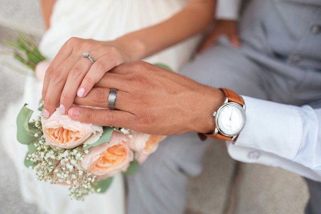 Couple holding hands over a wedding bouquet