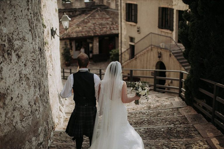Wedding couple walking down steps at Malcesine Castle, Lake Garda